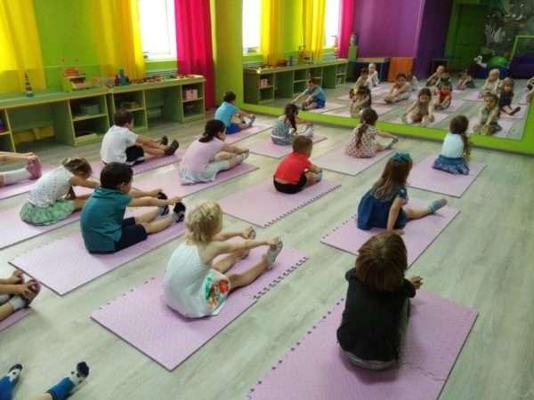 Дети выполняют упражнения, сидя на ковриках