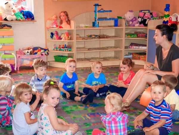 Воспитательница что-то рассказывает детям, сидящим на ковре