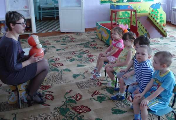 Воспитательница показывает матрёшку детям, сидящим на стульях