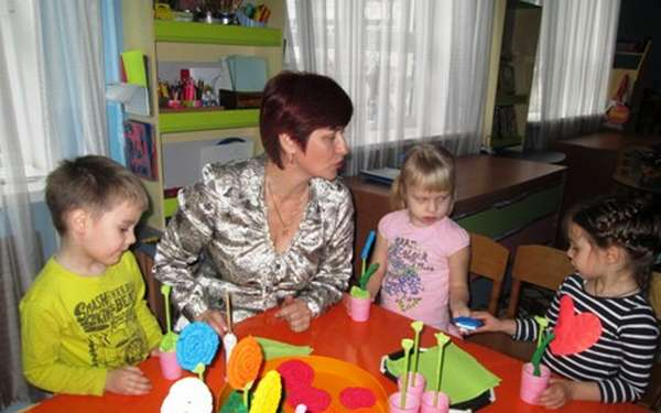 Воспитатель объясняет детям процесс изготовления поделок из бумаги