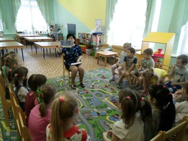 Педагог показывает картинку детям, сидящим на стульях
