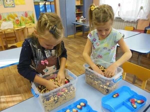 Две девочки выбирают игрушки из контейнеров с крупами