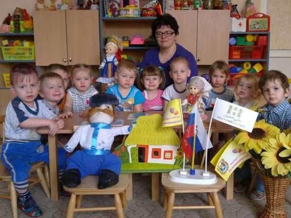 Педагог и малыши сидят за столом, перед ними — куклы и флаги