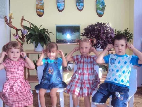 Четверо детей выполняют самомассаж ушных раковин