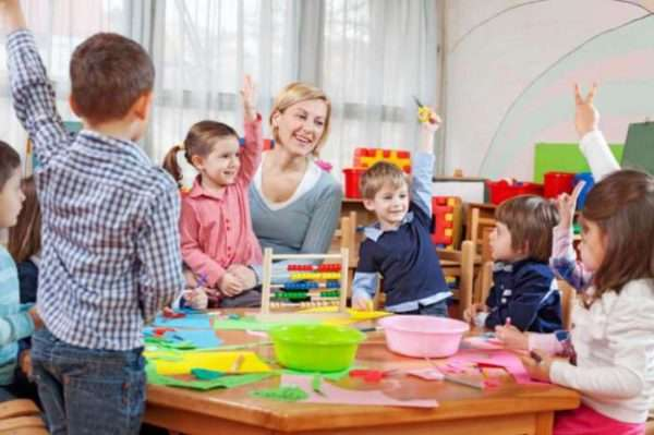 Воспитательница сидит за столом, рядом дети поднимают руки, чтобы ответить