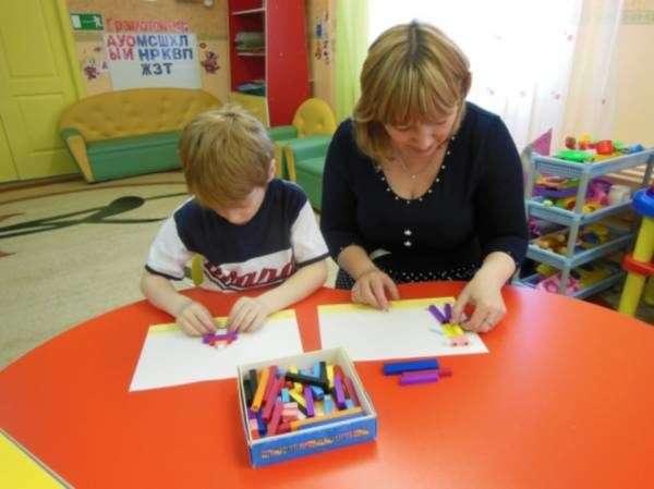 Мальчик и педагог складывают фигурки из палочек Кюизенера