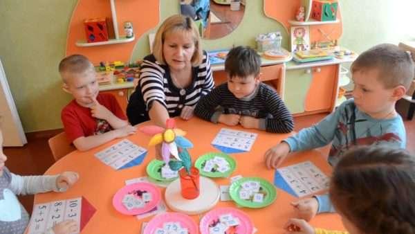 Воспитательница и дети за столом решают примеры