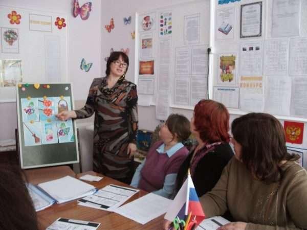 Воспитательница рассказывает что-то коллегам, сидящим за столом