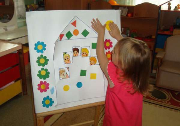 Девочка клеит солнышко около картинки домика с членами семьи