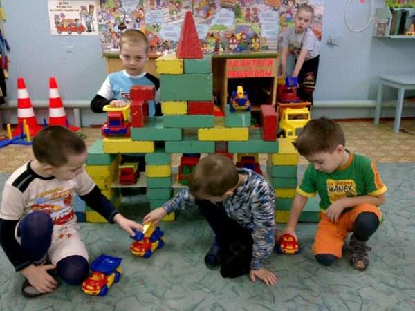 Мальчики построили большой гараж и играют с машинками