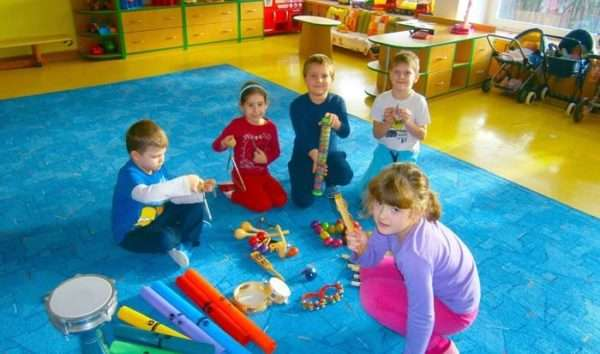 Дети, сидя на ковре, играют с музыкальными инструментами