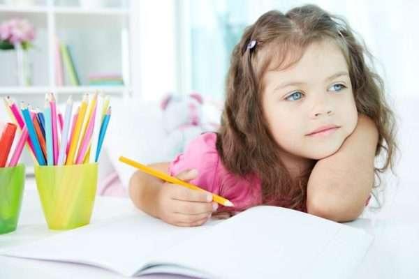 Девочка рисует цветными карандашами