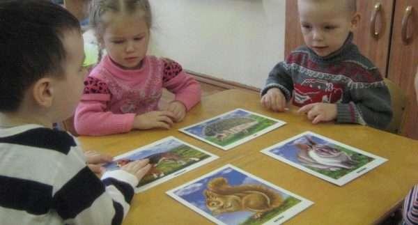 Дети сидят за столом, перед ними картинки с изображениями животных
