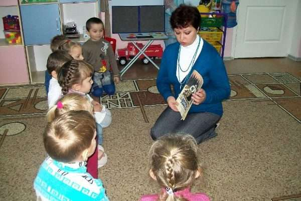 Воспитатель показывает детям, сидящим полукругом, картинку на книжке