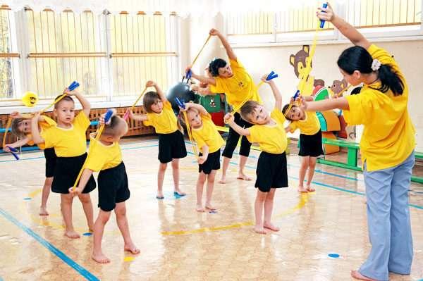 Дети с педагогом делают наклоны с гимнастической палкой