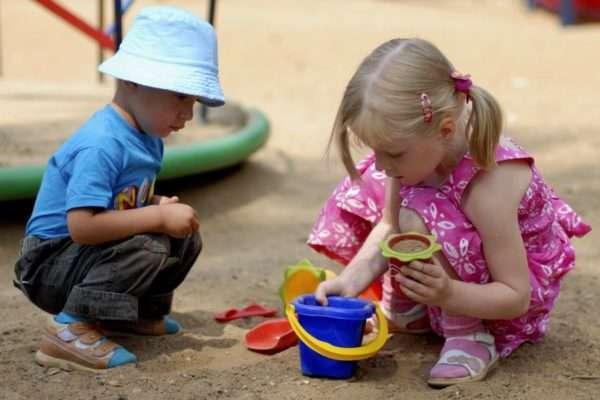 Дети общаются в песочнице