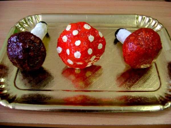 Готовые муляжи грибов, покрытые лаком, лежат на подносе