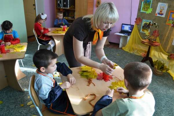 Педагог показывает детям, сидящим за столом, осенние листья
