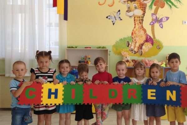 Дети держат большой пазл со словом children
