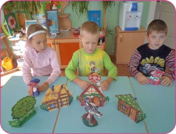 Трое детей с помощью настольного театра разыгрывают сказку «Три поросёнка»