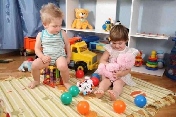 Девочка играет с плюшевым мишкой, мальчик сидит рядом