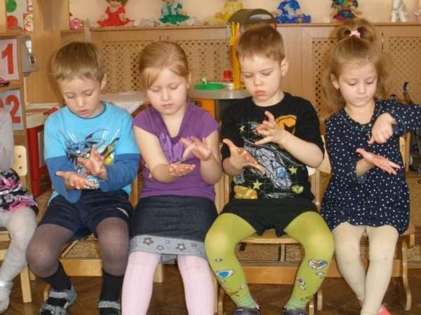 Четверо детей выполняют пальчиковое упражнение