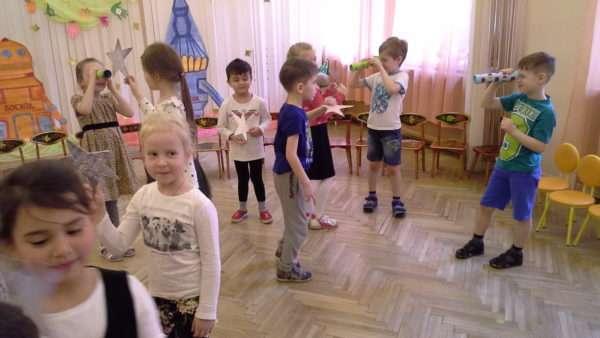 Дети ходят по залу со звёздочками и подзорными трубами в руках