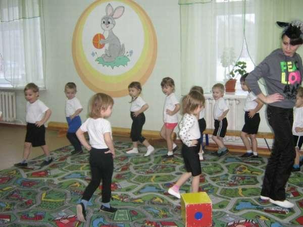 Дети и педагог в спортивной форме идут по кругу