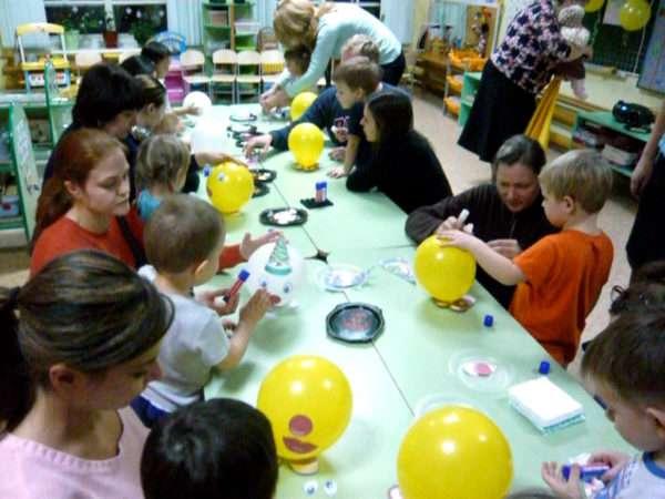 Дети и родители делают человечков из воздушных шариков