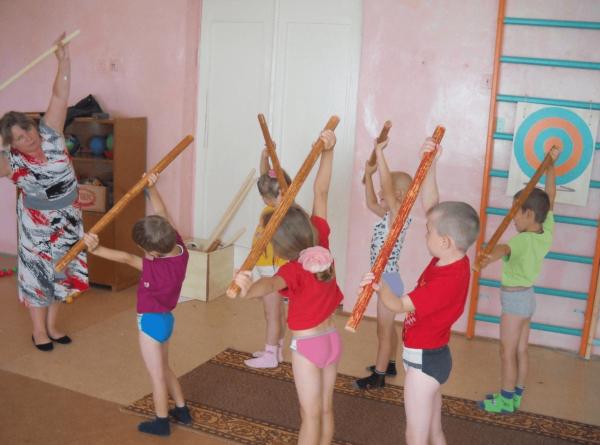 Дети выполняют упражнение с палками в спортивном зале