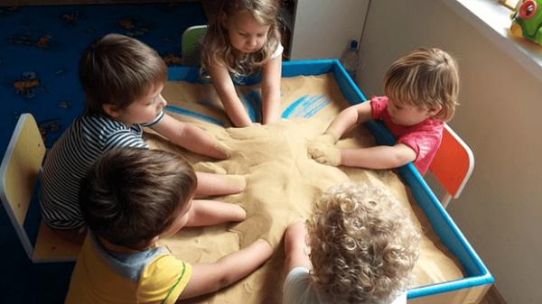 Дети занимаются песочной терапией в группе