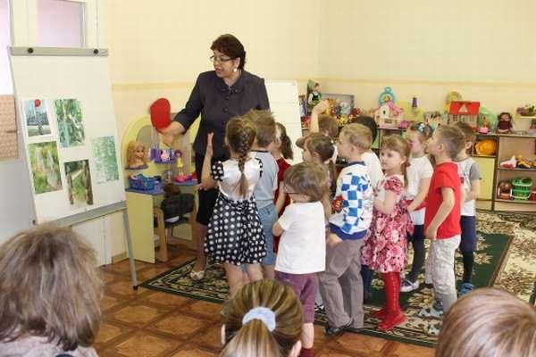 Дети с воспитательницей рассматривают картинки на магнитной доске