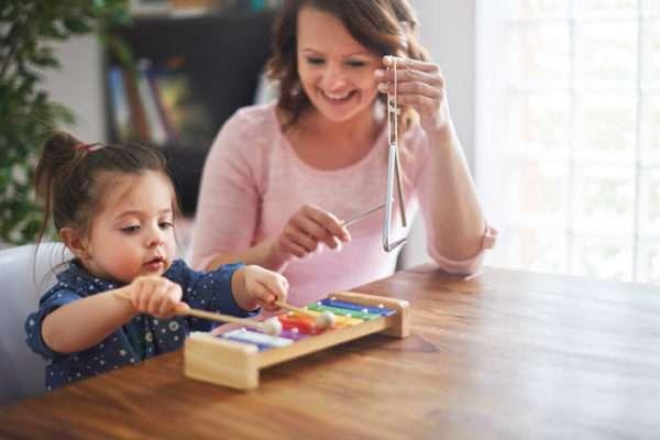 Педагог развивает слух ребёнка с помощью игры на ксилофоне