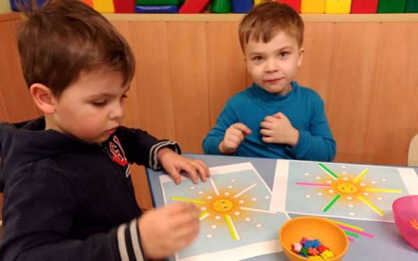 Мальчики выкладывают палочками лучи солнца