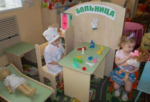 Две девочки играют с куклами в больницу