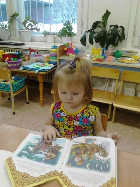 Девочка рассматривает книгу в детском саду