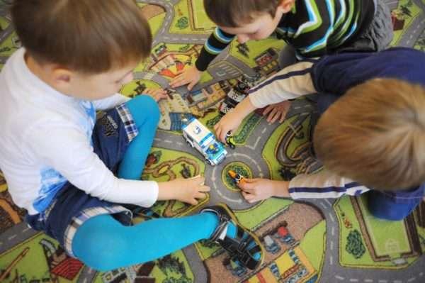 Три мальчика, сидя на ковре, играют с машинками