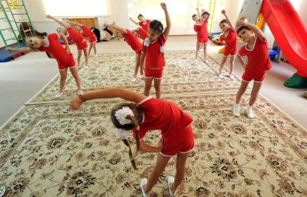 Дети в красной спортивной форме делают зарядку