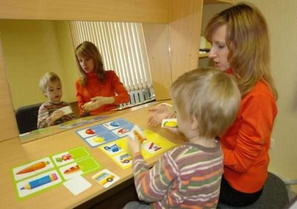 Мальчик и педагог работают с разрезными картинками