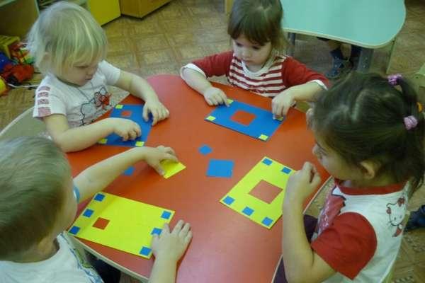 Четверо детей вкладывают разного размера квадраты в подходящие отверстия на листах, лежащих перед ними