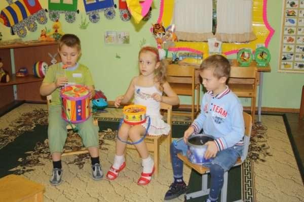 Два мальчика и девочка играют на барабанах