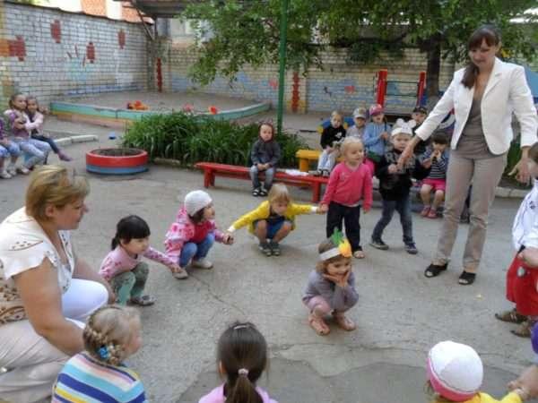 Педагоги в хороводе с детьми на площадке приседают и встают