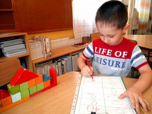 Мальчик фиксирует количество использованных деталей постройки в технологической карте