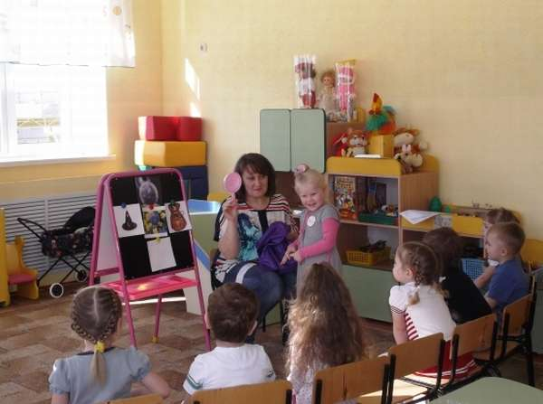 Воспитательница держит зеркало из волшебного мешочка на коленях, рядом стоит девочка