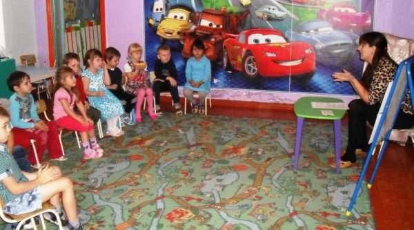 Дети сидят полукругом и беседуют с воспитательницей