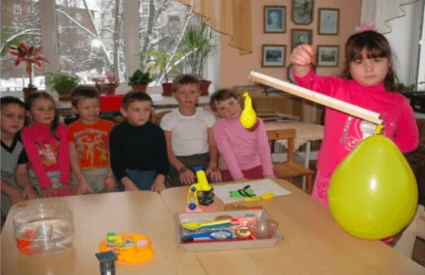Девочка держит в руках импровизированные весы с воздушными шарами, остальные дети наблюдают