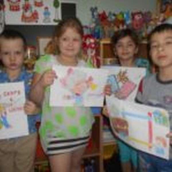 Четверо детей держат рисунки