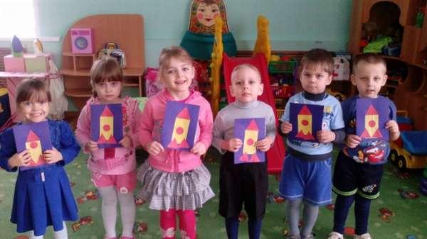 Шестеро детей стоят с аппликациями ракеты в руках