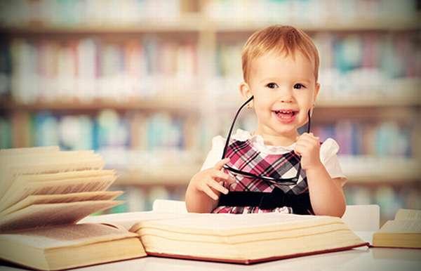 Маленькая радостная девочка среди книг