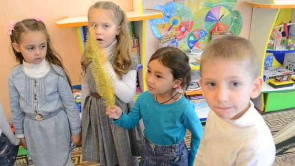 Четверо детей стоят, одна девочка с жёлтым пером